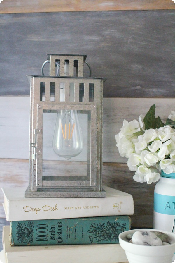 DIY Lantern with antique light bulb lamb, staged on books with jar of flowers, a perfect DIY rustic farmhouse home decor project when you're on a tight budget