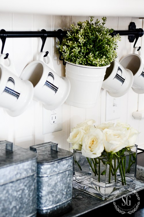 Black kitchen hanging rack with coffee cups set above kitchen counter with galvanized canisters, a perfect DIY rustic farmhouse home decor project when you're on a tight budget