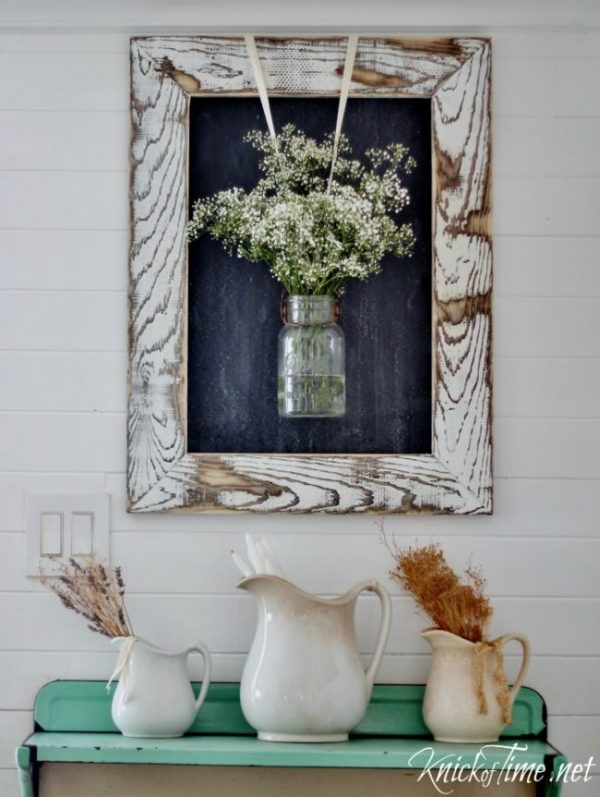 DIY rustic frame with chalkboard, with hanging mason jar and baby's breath, above buffet table with ceramic pitchers, a perfect DIY rustic farmhouse home decor project when you're on a tight budget
