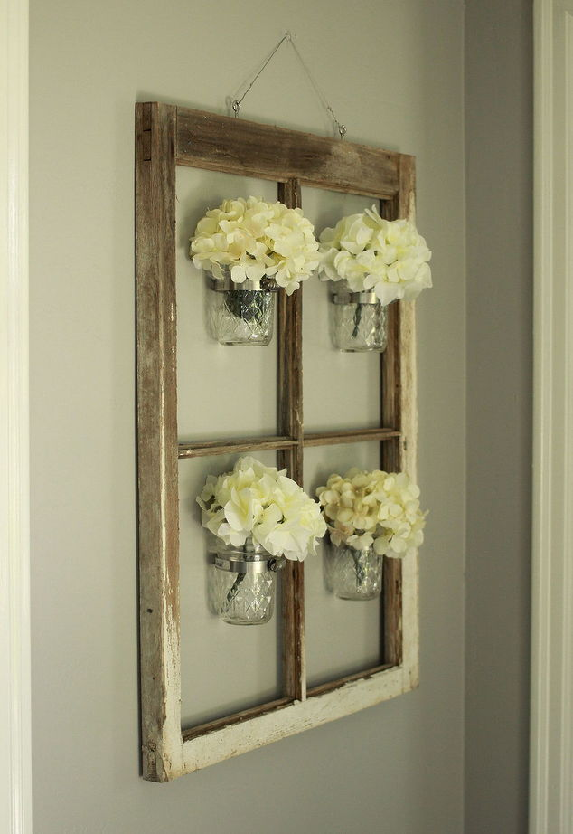 Old window hung with mason jar vases full of hydrangeas as well decor, idea for decorating with vintage windows