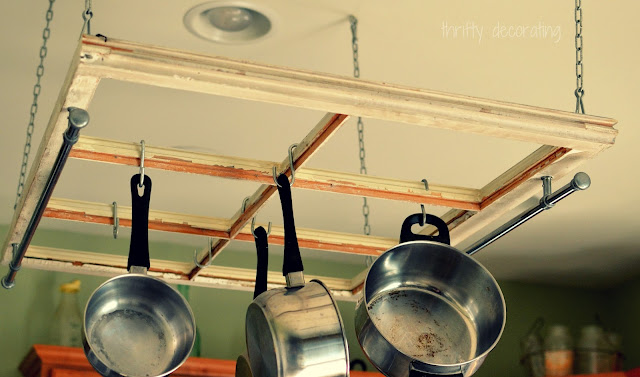 Old window hung flat from ceiling as a pot and pan holder, idea for decorating with vintage windows