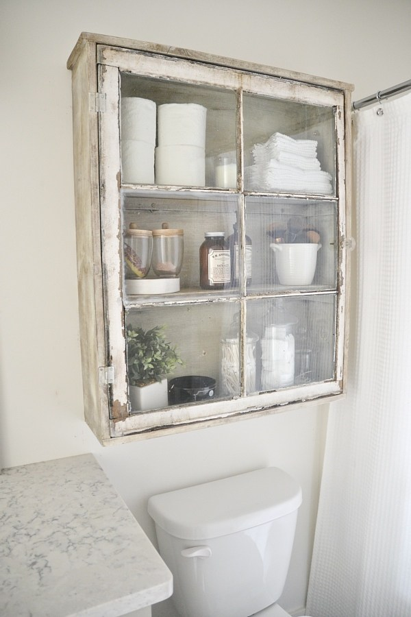 Old window repurposed as a cabinet door for bathroom cabinet, idea for decorating with vintage windows