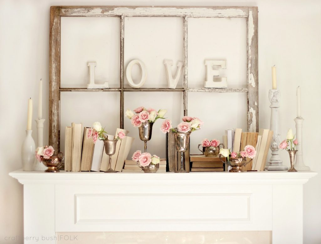 Old window on mantel with LOVE letters and pinks flowers and old books and vases, idea for decorating with vintage windows