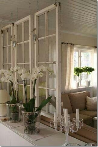 Old windows hung vertically to separate rooms as a partition, idea for decorating with vintage windows