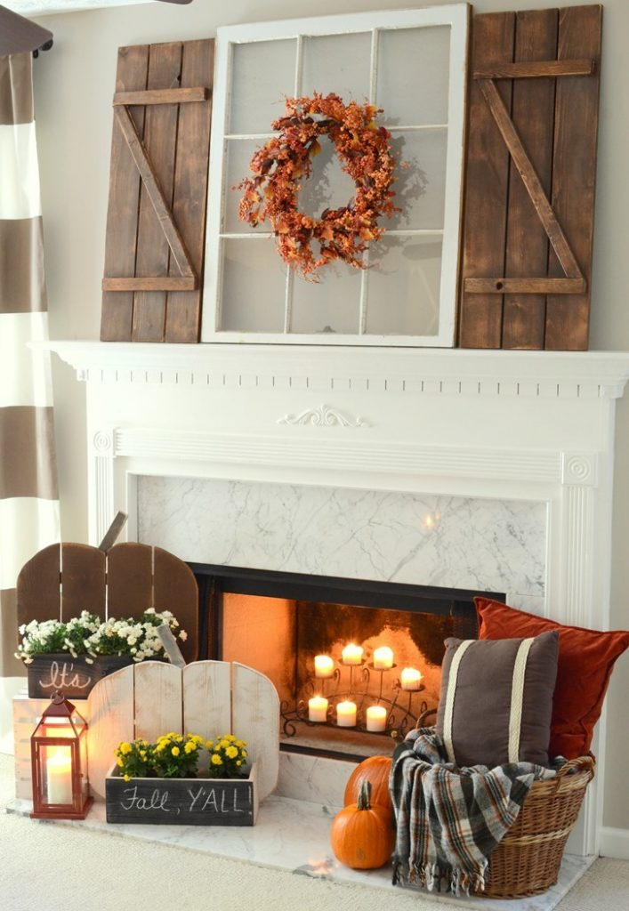 Fall mantel with window pain with wreath and wood shutters, wooden pumpkins, candles, lanterns, flowerboxes, and basket with pillows and blankets on bottom