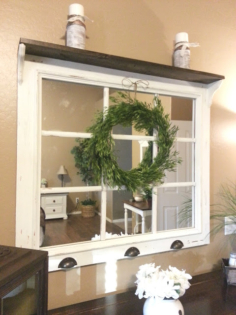 Old window repurposed with shelf on top and mirrors in panes with wreath, idea for decorating with vintage windows