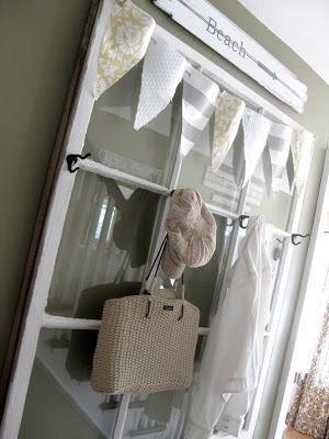 Old window repurposed with hooks as a coat and bag rack, idea for decorating with vintage windows