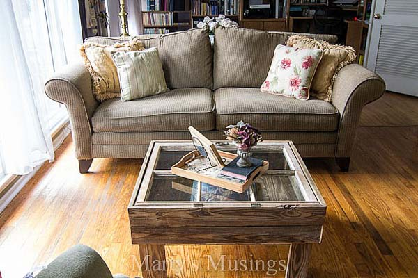 Old window repurposed as a living room coffee table, styled with books on top in front of couch, idea for decorating with vintage windows