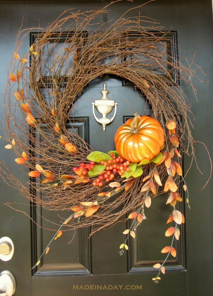 DIY fall wreath with hurricane style branch with orange twig flowers, berries and pumpkin