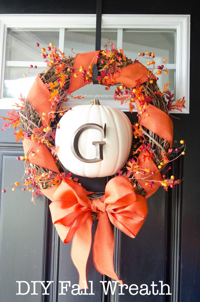 DIY fall wreath, grapevine wreath loosely wrapped with orange ribbons, berries and leaves, with cream monogrammed pumpkin in center