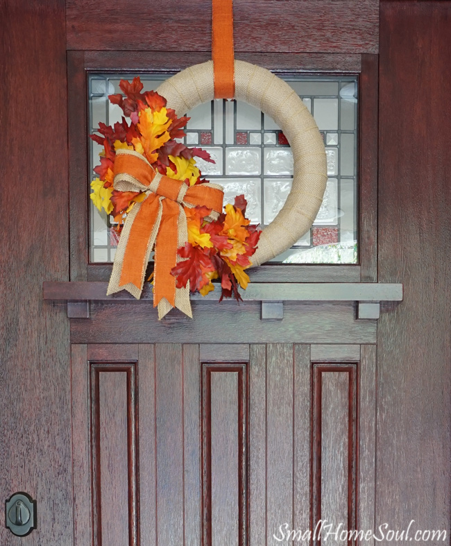 DIY fall wreath covered with cream burlap ribbon and faux gold, yellow rust leaves with orange burlap bow