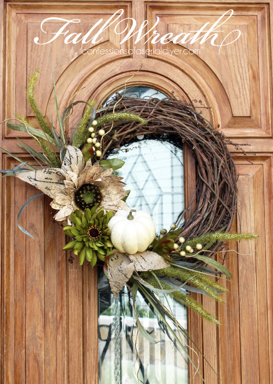 Woodsy fall DIY wreath with green and neutral flowers and pumpkins on a grapvine wreath