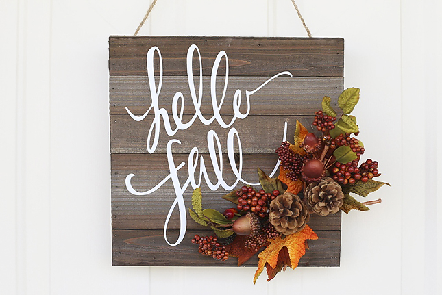 DIY Hello Fall sign on reclaimed wood with faux pine cones, berries and fall leaves