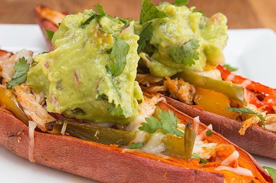Chicken fajita sweet potato skins topped with guacamole and cilantro, one of my favorite Whole30 dinner recipes