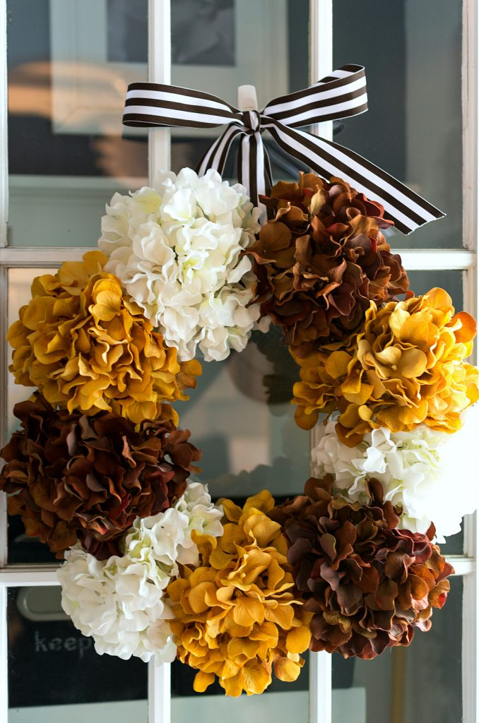 DIY fall wreath with faux brown, gold, cream hydrangeas with brown and white striped ribbon