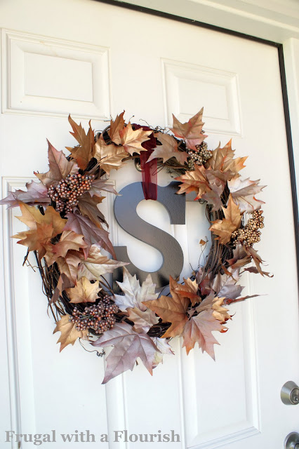 DIY fall wreath with metalic brown and gold flowers and berries on grapevine wreath with monogram center