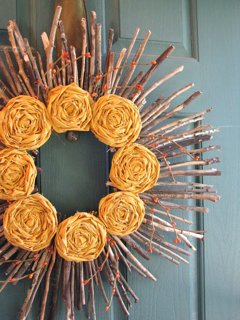 DIY fall wreath made with sticks and faux gold rosettes and berries