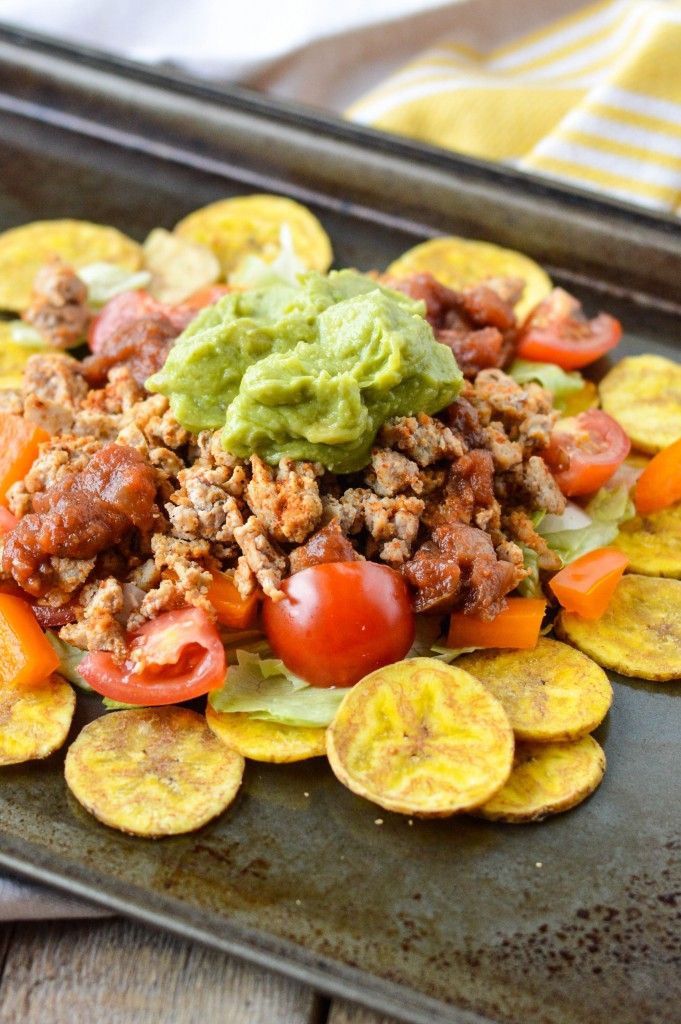 Close up of ground turkey plantain nachos topped with guacamole, ground turkey, cherry tomatoes, one of my favorite Whole30 dinner recipes