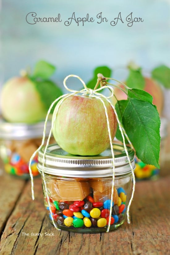 DIY mason jar gift with M&Ms and caramel inside and an apple tied to the top, for a caramel apple gift jar