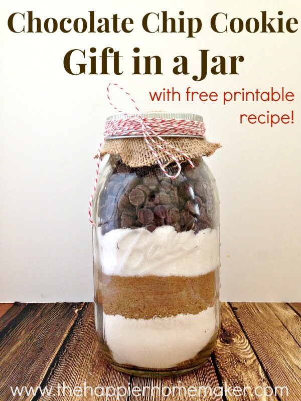 Mason jar DIY Christmas gift filled with chocolate chip cookie ingredients with burlap and bakers twine at the top, on wooden table