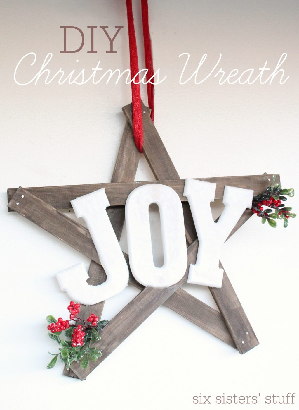 DIY farmhouse Christmas JOY door hanging on stop of wooden star with berries and greens