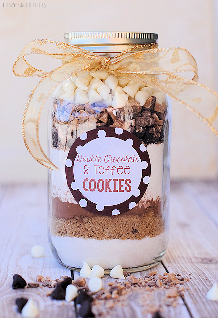 Mason jar DIY Christmas gift filled with ingredients for double chocolate and toffee cookies, with gift label and gold bow set on table