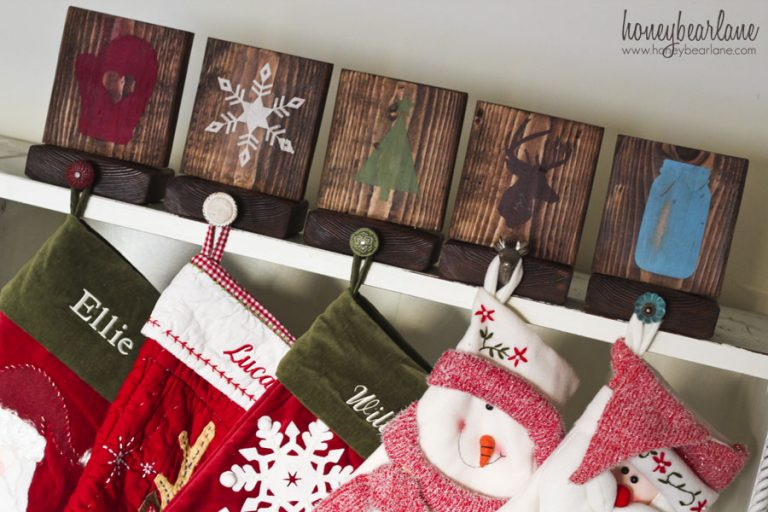 DIY farmhouse Christmas wood block stocking holder with Christmas images painted on (mittens, snowflakes, Christmas tree), with knobs attached and stockings hanging