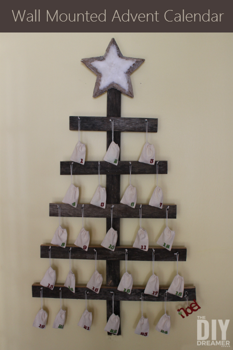 DIY farmhouse Christmas wall-mounted Advent calendar in shape of Christmas tree with small burlap number bags hanging from cross sticks