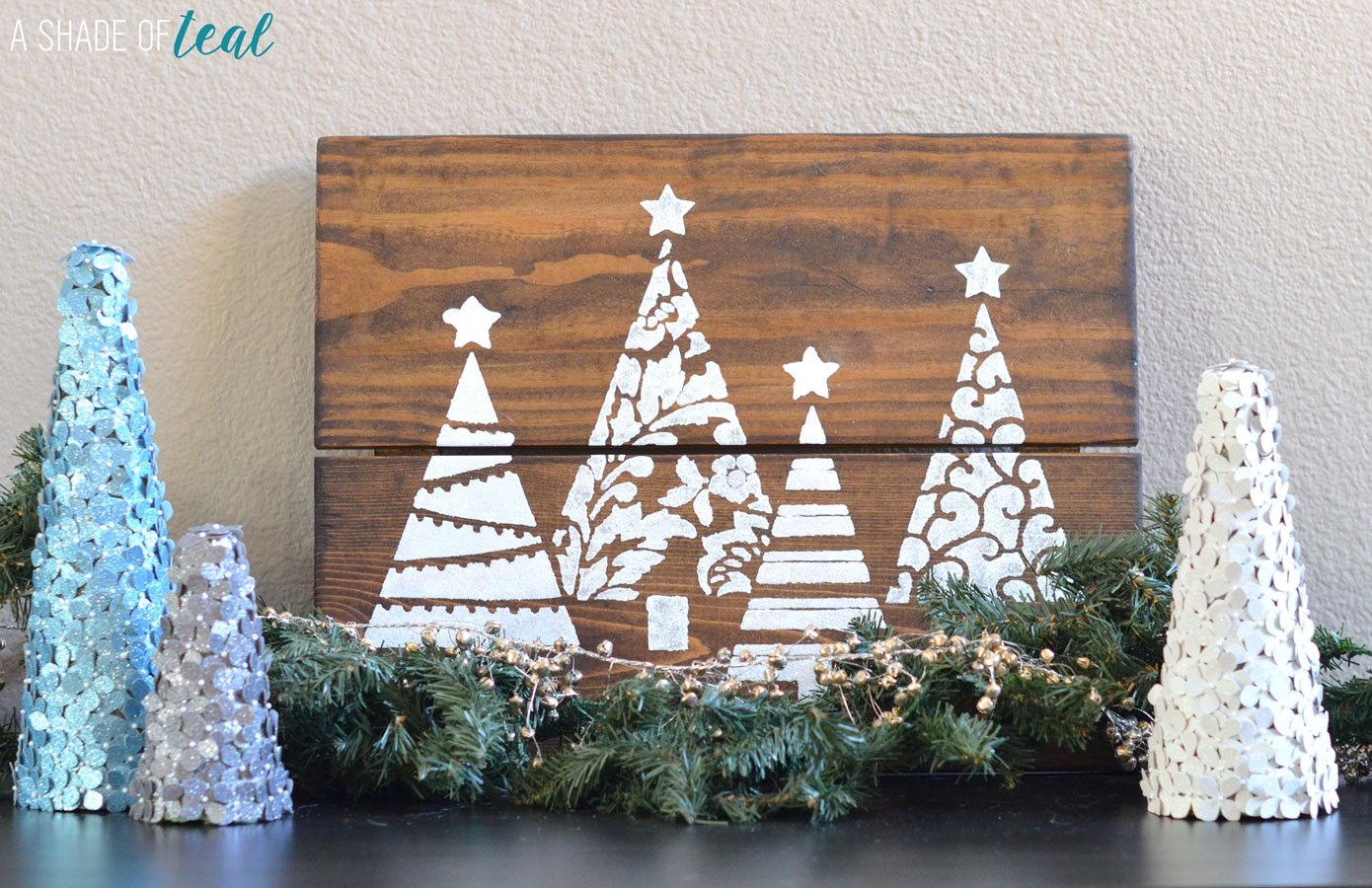 DIY farmhouse Christmas project stenciled Christmas trees on reclaimed wood with garland and glitter trees surrounding