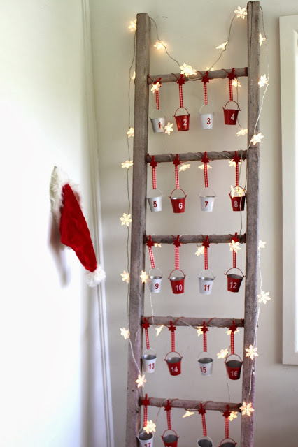 DIY Advent Christmas Calendar with blanket ladder and red and white numbered mini pails hanging from gingham string with snowflake lights