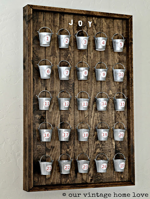 DIY Christmas Advent Calendar, rustic wood background and frame with mini galvanized pails hung in rows with numbers