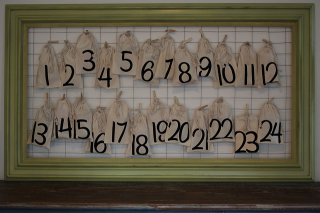 DIY Advent Christmas calendar made from chicken wire in a frame with small burlap sacks that are numbered and tied on.