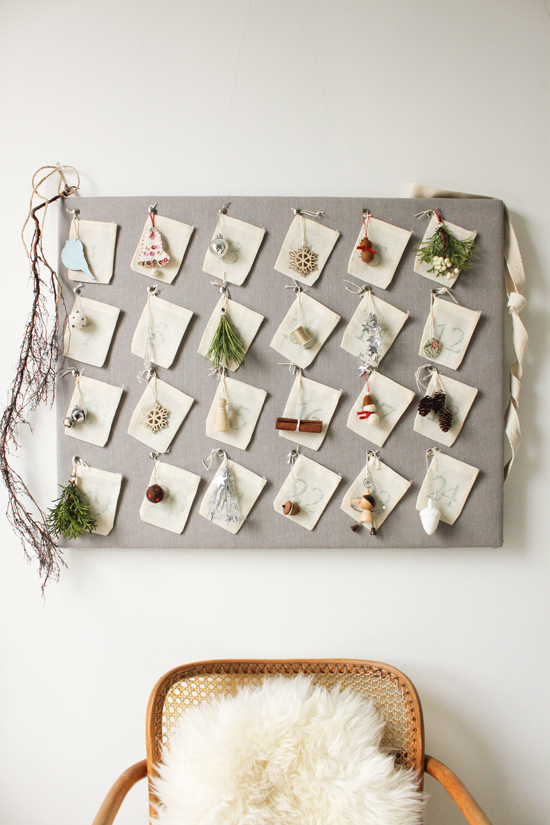 DIY Advent Calendar on grey fabric covered board with small linen sacks with small vintage ornaments hanging