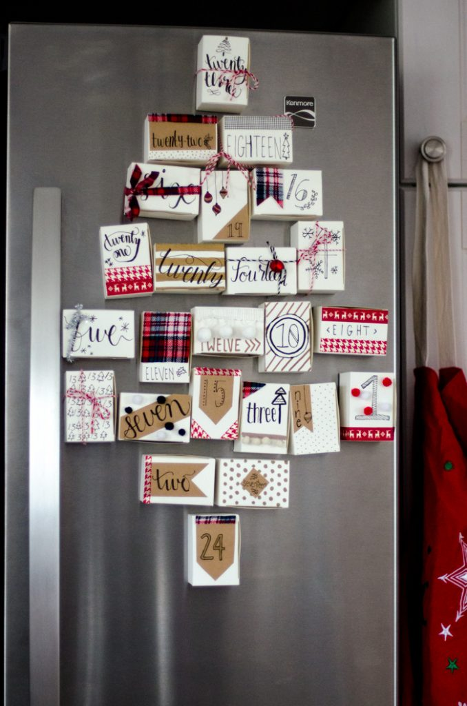 DIY Magnetic Christmas Advent Calendar with decorated and numbered jewelry boxes on the refrigerator in shape of Christmas tree