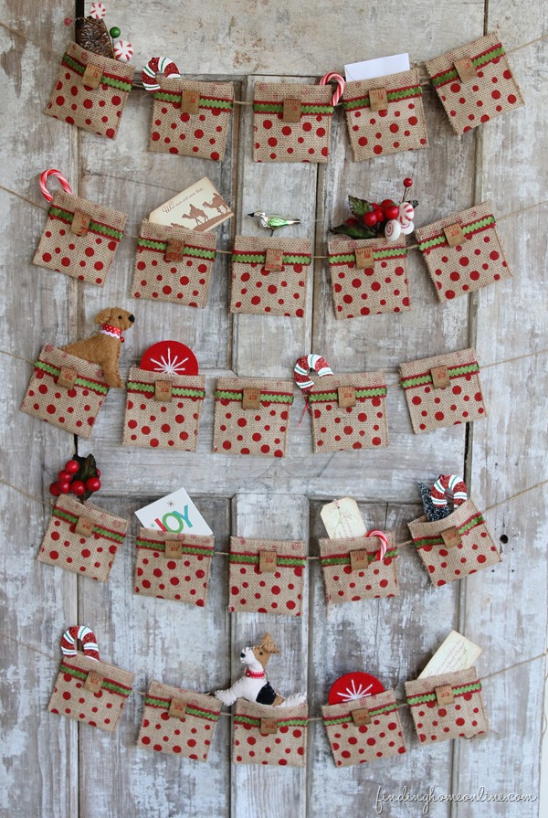 DIY Christmas Advent calendar with red dotted mini burlap sacks strung in rows on jute strings, with Christmas decorations come out of the top, on rustic barnwood background
