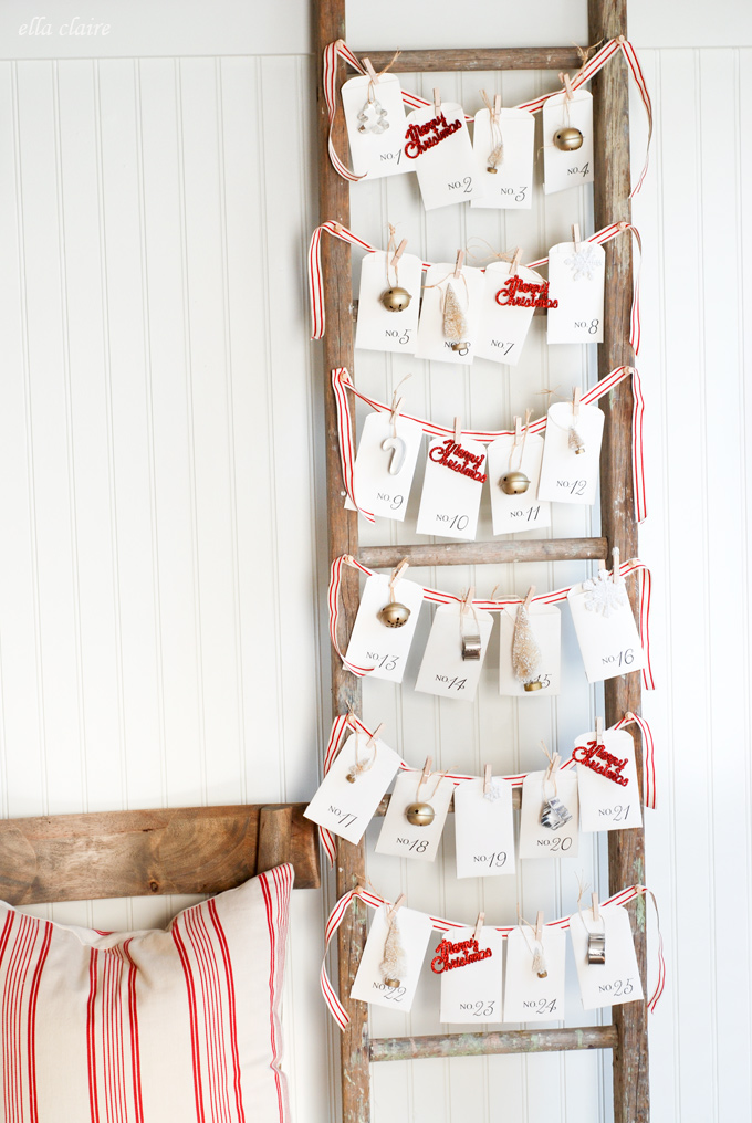 DIY Advent Calendar wooden ladder with striped red ribbon hanging across and vintage tags with small ornaments