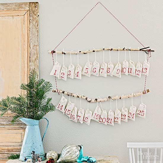 DIY Christmas Advent Calendar, rustic branches hung in 2 rows with mini white linen sacks hanging from them with red numbers, hung on wall