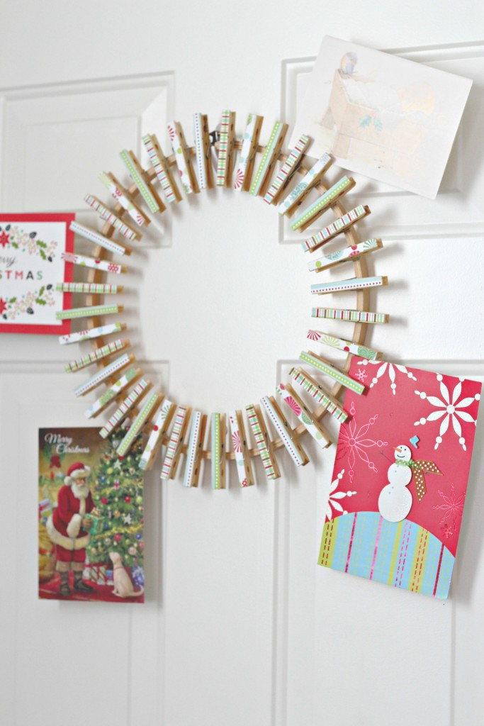DIY Christmas card display holder of a clothespin wreath that hold Christmas cards