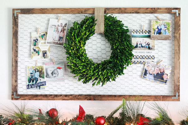 DIY Christmas card display holder of wooden frame with chicken wire, wreath in center with cards attached with clothespins