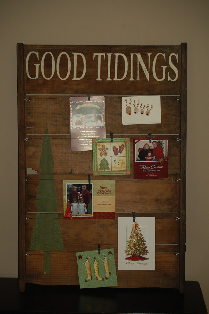 DIY Christmas cardholder display of wooden sign 'Good Tidings' at the top with string horizontally in lines with cards attached by mini-clothespins