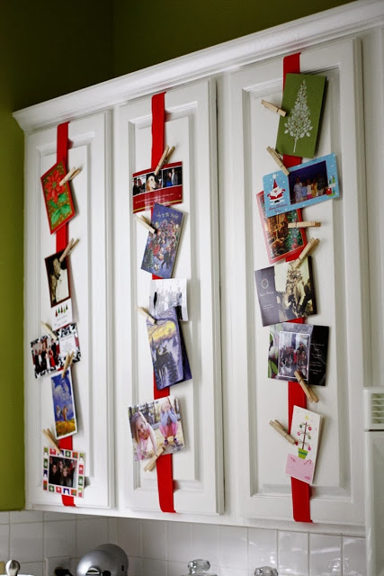 Diy Christmas card holder display with ribbons on kitchen cabinets and cards attached with clothes pins