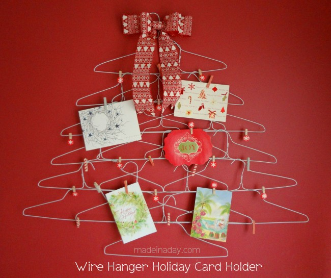 DIY Christmas card holder made of wire hangers in the shape of a tree, with a bow on top, Christmas cards are attached with mini-clothespins
