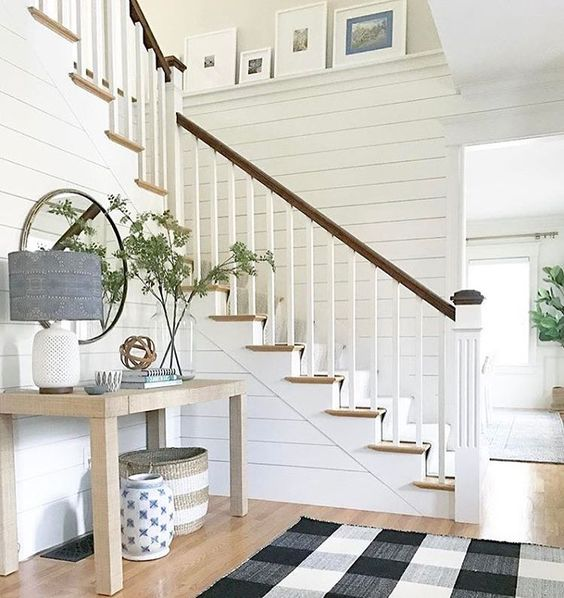 Entryway staircase with console table and buffalo check rug