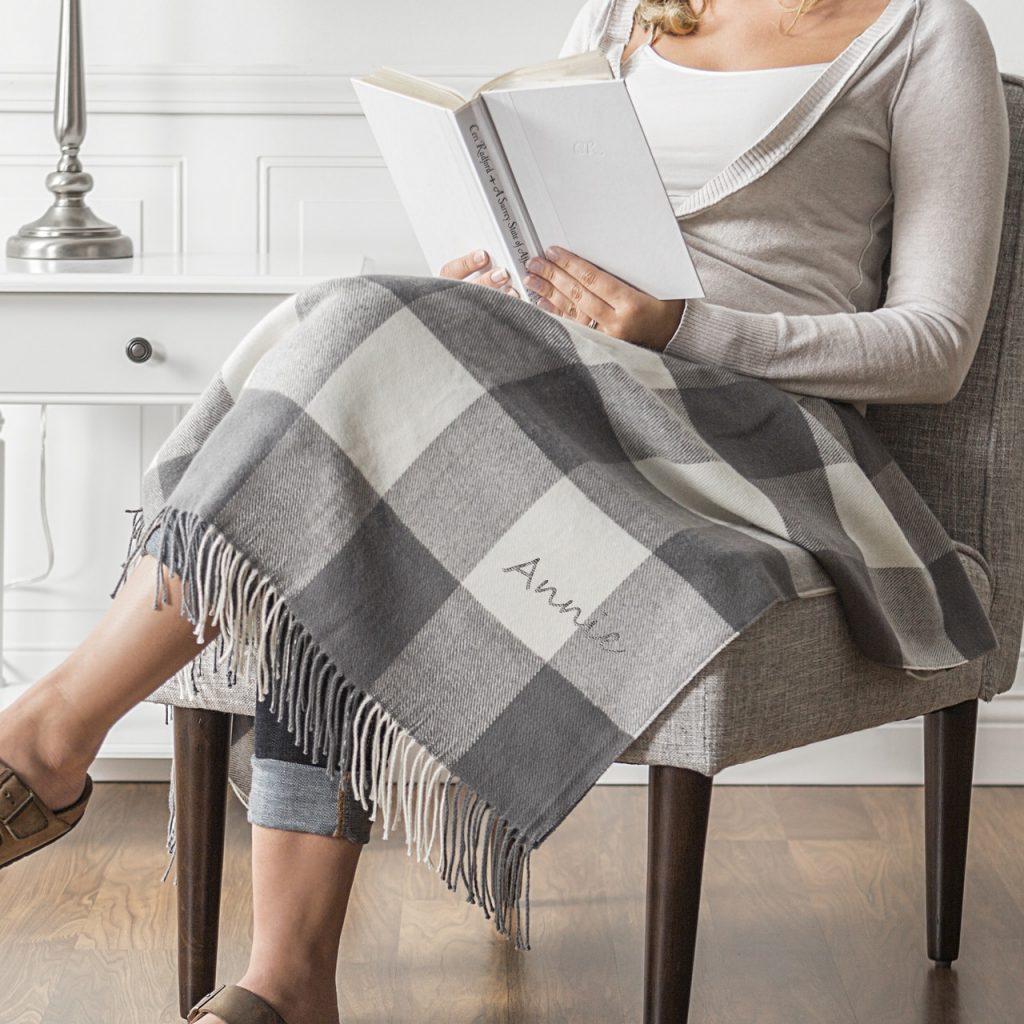 Woman on chair reading, covered with gray buffalo check blanket