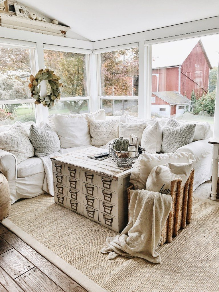 Cozy winter white couch and living room with apothecary coffee table and basket with pillows and blankets