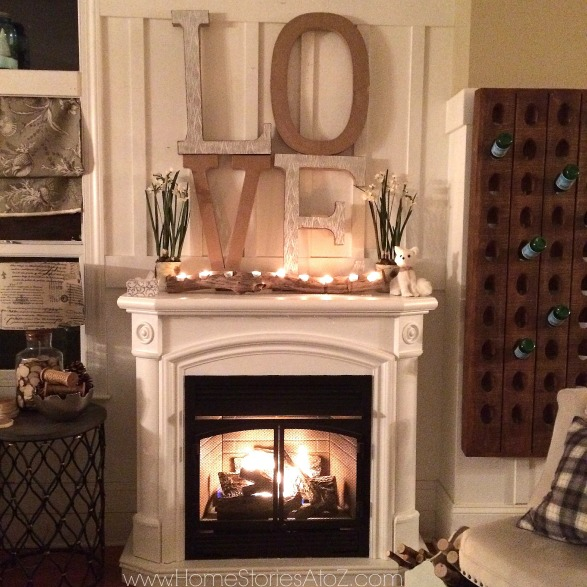 Winter mantle and fireplace with wooden LOVE sign, plants and lighted log on top