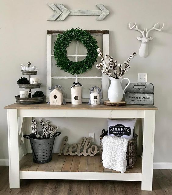 Console table styled with olive bucket and cotton stems, woven basket with blanket and pillow, vintage window with wreath, 3 tier tray, white pitcher with cotton stems
