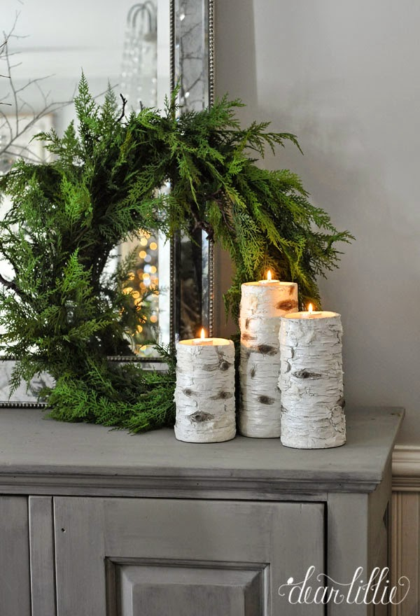 Birch candles with evergreen wreath on console table