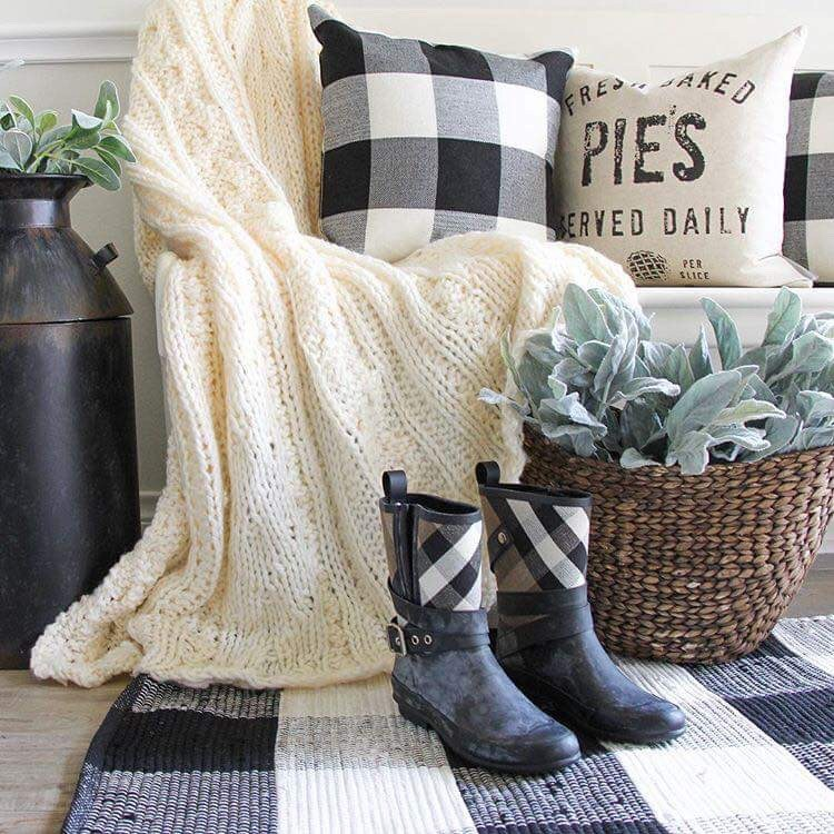 Entry bench with knit blanket, buffalo check pillow, boots, and rug, farmhouse pillow, woven basket with lambs ears