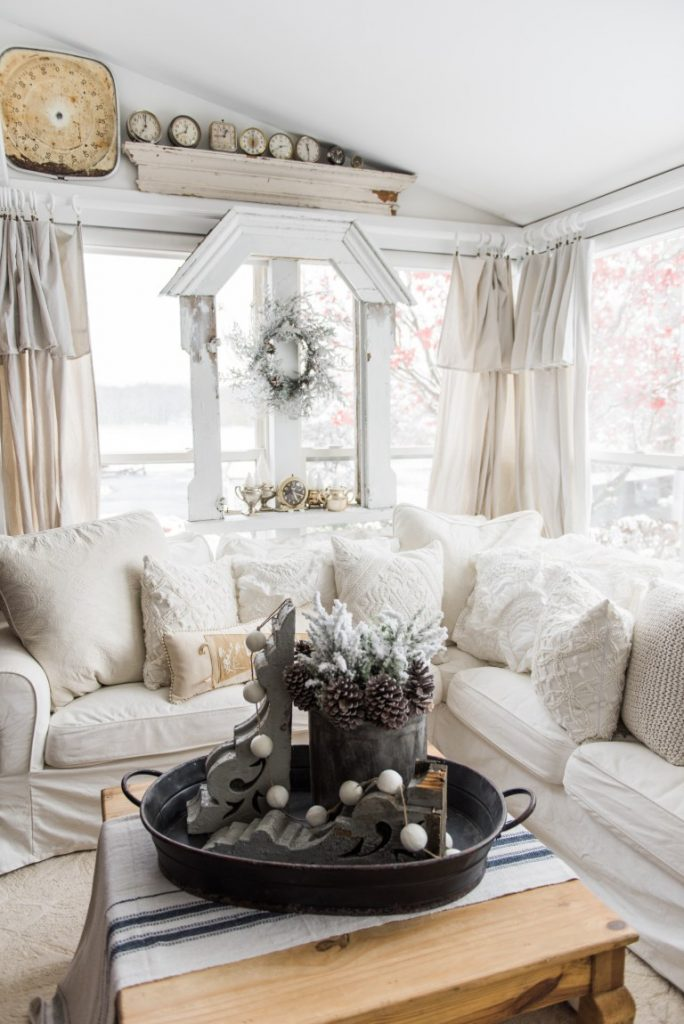 Cozy winter white couch with tray on coffee table with pail of pinecones and greens